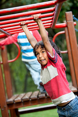Boy playing at the park on the monkey bars