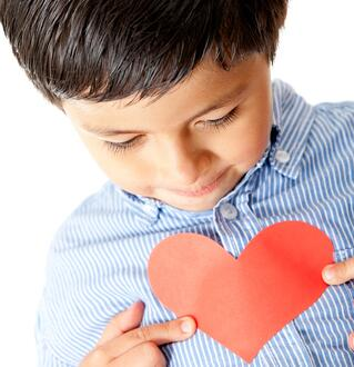 Boy holding a red heart for Valentines Day - isolated.jpeg