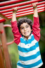 Boy playing at the monkey bars and smiling-2